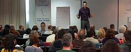 תמונה של אריאל בהרצאה עומד מול קהל