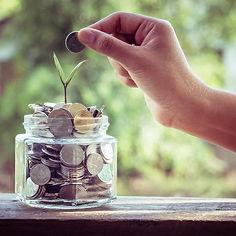 תמונה בשחור לבן עגולה של צנצנת עם כסף ושתיל קטן ויד שרוצה לשים בצנצנת מטבע