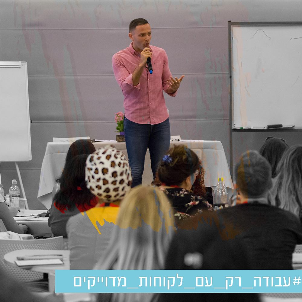 תמונה של אריאל מרצה מול קהל בשחור לבן  עם משיכת מכחול שחושפת צבע