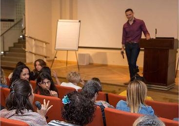 אריאל עומד על במה בכנס הסנדול ורואים את הקהל ובקהל יש בחורה שמדברת עם מיקרופון
