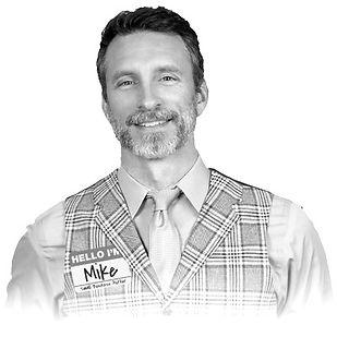 תמונה של מייק מיקאלוויץ מסתכל למצלמה בצורת עיגול בשחור לבן