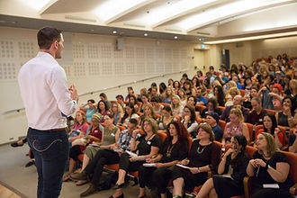תמונה של אריאל עומד מול קהל בכנס שלו