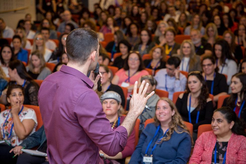 תמונה של אריאל מדבר בכנס שרואים את הקהל ואת הגב של אריאל