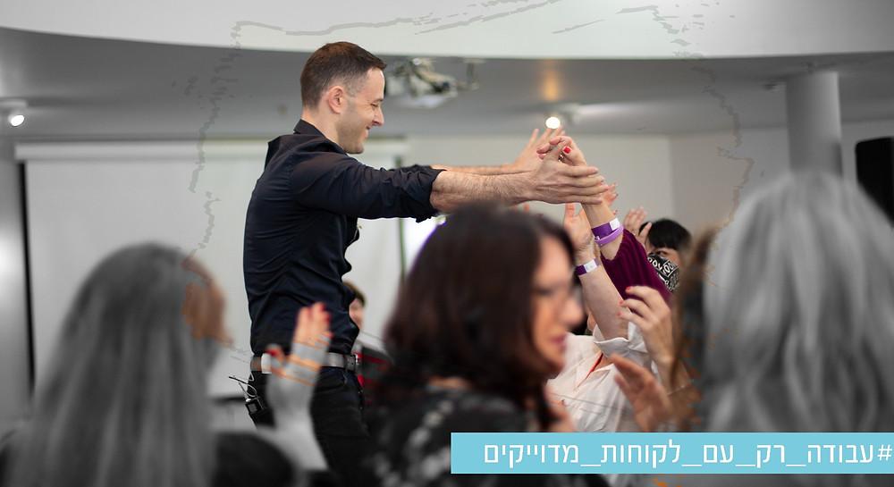 תמונה של אריאל בכנס שלו רוקד יחד עם הקהל בשחור לבן  עם משיכת מכחול שחושפת צבע