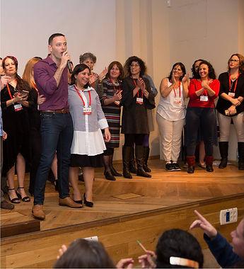 אריאל בכנס הסינדול עומד על הבמה מחבק מישהי מהקהל ומאחוריו קבוצה של אנשים