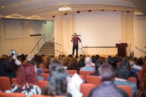 תמונה של אריאל בכנס הסינדול מדבר מול קהל