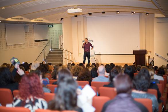 תמונה של אריאל בכנס הסנדול עומד ומדבר מול קהל