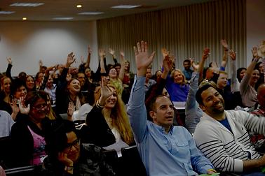תמונה של אנשים בקהל מרימים את היד למעלה