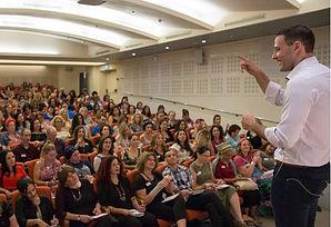תמונה של אריאל בכנס עומד מול קהל