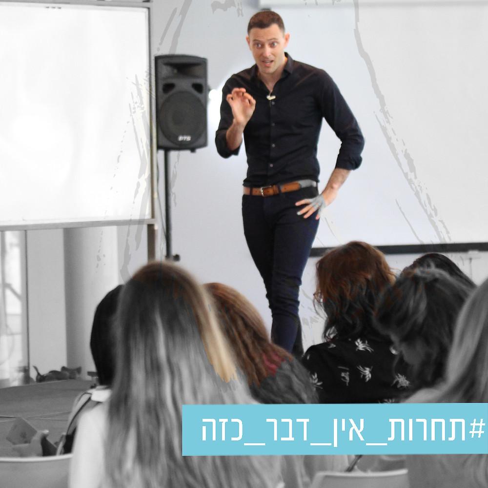 תמונה של אריאל בכנס מול קהל בשחור לבן  עם משיכת מכחול שחושפת צבע