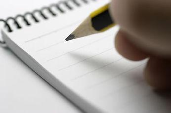 תמונה של יד אוחזת בעיפרון שבאה לכתוב בפנקס