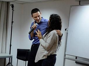 תמונה של אריאל בכנס מדבר עם מישהי מהקהל על הבמה