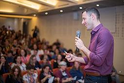 תמונה של אריאל מתוך הכנס שלו עומד מול קהל ומחייך