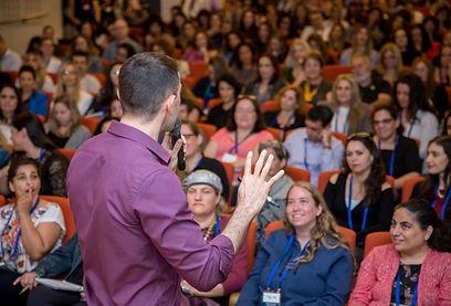 תמונה של אריאל מפנה את הגב למצלמה עומד מול קהל ומדבר בכנס