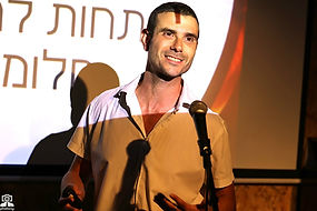תמונה של דניאל בן ארי עומד מול מיקרופון