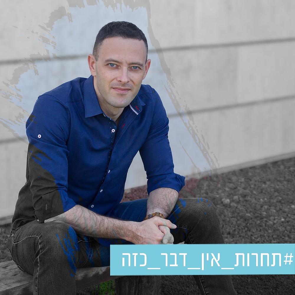תמונה של אריאל בשחור לבן יושב מול המצלמה עם משיכת מכחול  שחושפת צבע