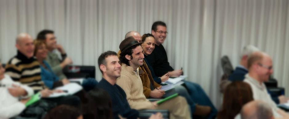 תמונה של שורה מתוך קהל שיושבים מחייכים וצוחקים