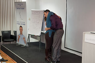 תמונה של אריאל בהרצאה מחבק מישהי מהקהל