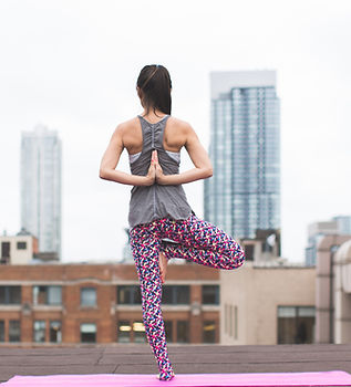 woman-standing-on-pink-yoga-mat-meditati