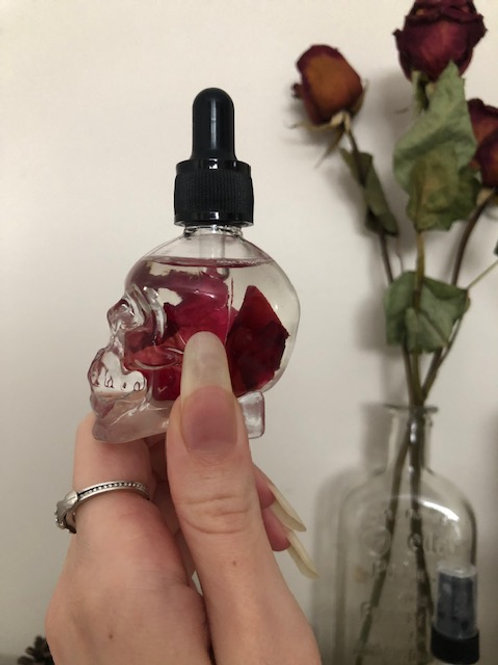 Glass skull dropper bottle with organic rose petals