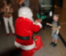 Santa giving reindeer antlers to child