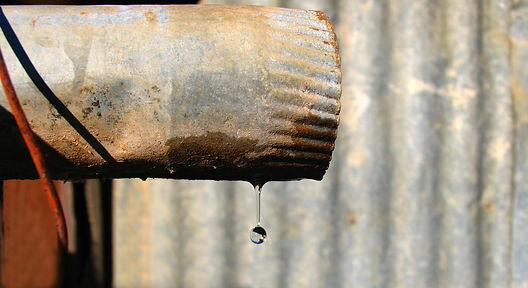 Susan Segal The Last Drop. rusty pipe against a corrugated iron backgroound with a dprop of water
