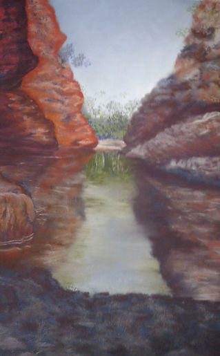 Wendy Moore - Simpsons Gap.jpg close view of orange and brown cliffs with water between.