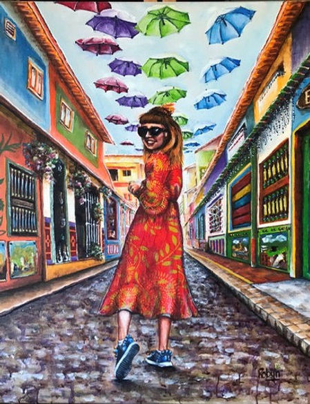 Robyn Carr Columbian Beauty.j Girl in a red pattermed dress walking down an arvare with a canopy of umbrellaspg