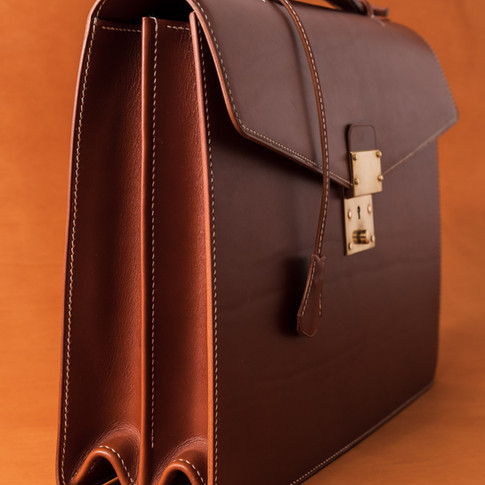 Double gusset briefcase in Chestnut Veg tan form Tuscany. Solid brass hardware handmade in England. Stainless runner under handle for strength and reinforced vertical panels for added durability and to prevent sagging. Fully lined with black pigskin. Made to order- Contact me for details.