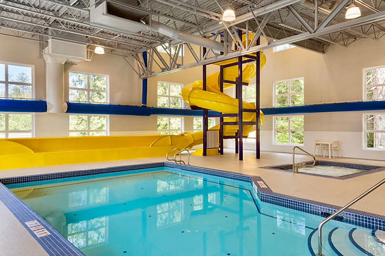 Swimming Pool Microtel Inn & Suites, Oyster Bay, Ladysmith, White Tile, Yellow Waterslide, Fabric HVAC Duct,  Spa. Blue tile freeboard, White Tiled Pool, Stainless Steel Handrail, Inlays TIle, Depth Markers, Pool Nosing