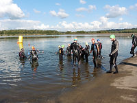 Photo of group of swimmers in wetsuits entering the water