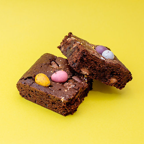 two Mini Egg topped brownies on a yellow background