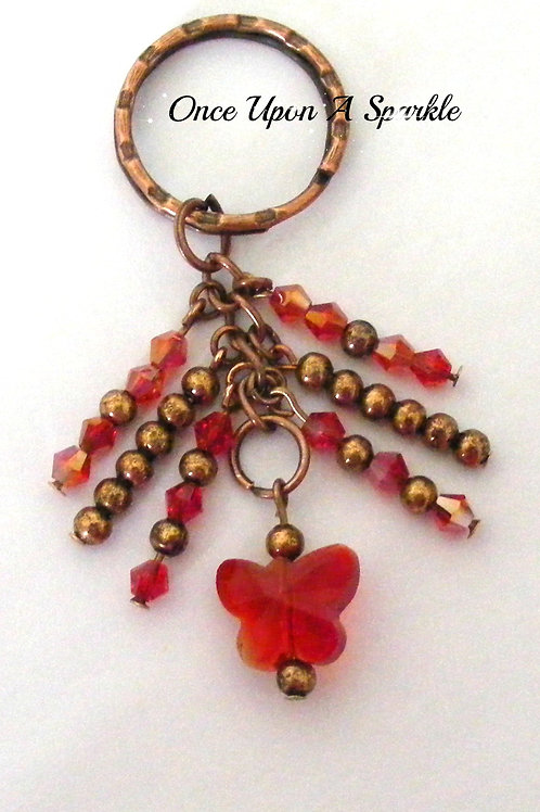copper beads with sparkly red beads and red butterfly