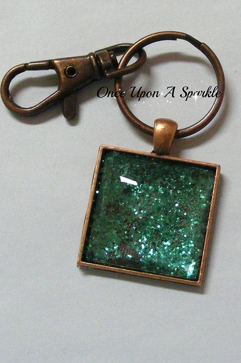 copper square bezel tray with green glitter under dome