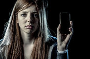 A teen holds a cell phone and she is clearly unhappy.