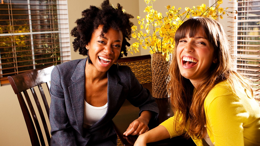Diversity, two women at a table laughing.  mysmallbank.com