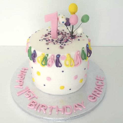 babys 1st bday birthday cake covered in sprinkles and pastel colours