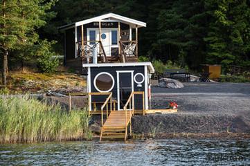Lilla stugan Bryggan med den vedeldade bastun precis vid sjökanten