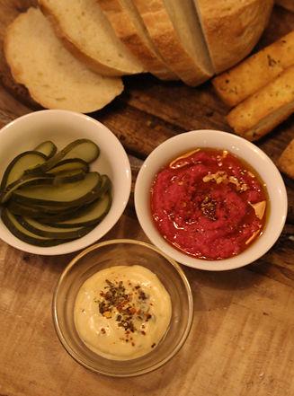 pickles de pepino, hummus de remolacha, dip cremoso, pan casero, pan de pizza
