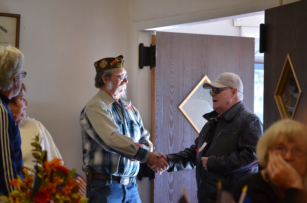 Veterans welcome each other at the door.