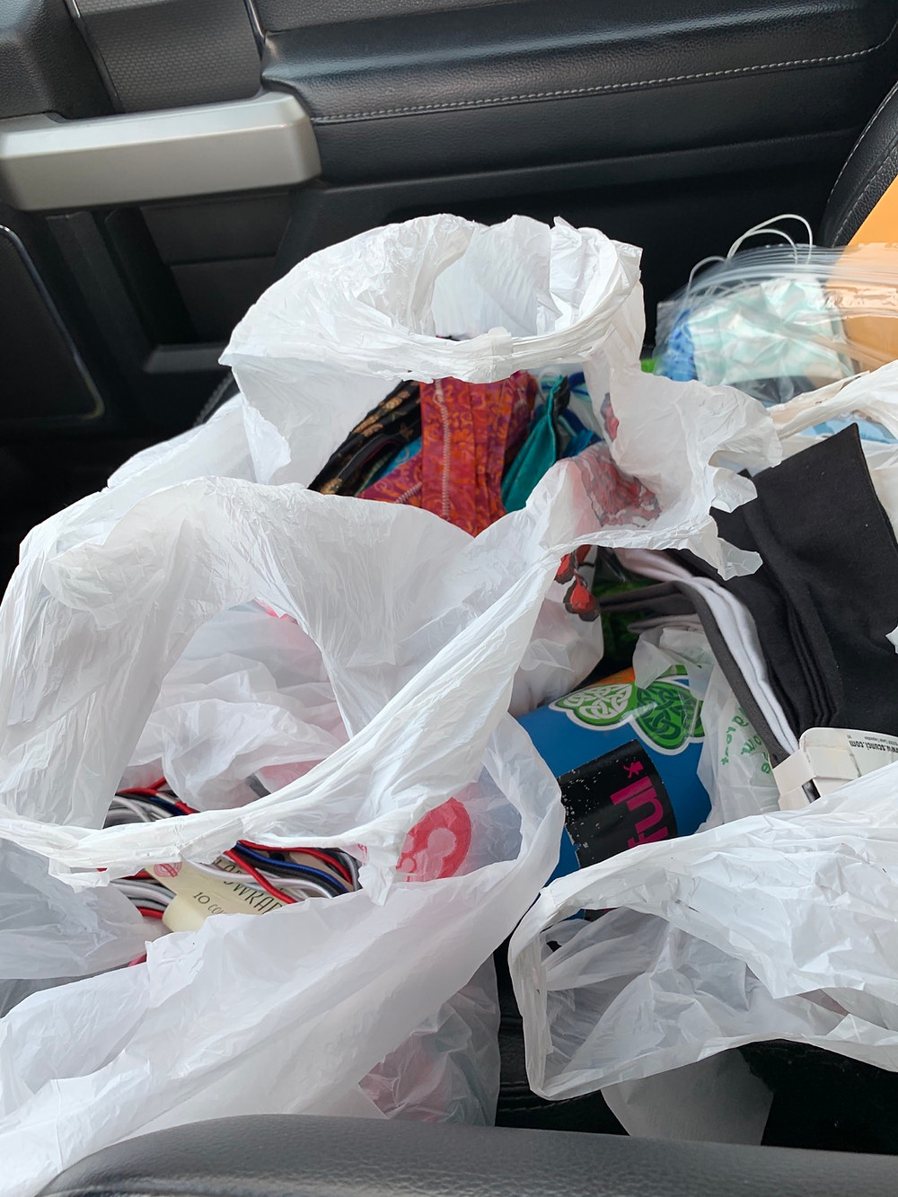 The bags filled with sewing supplies and finished masks that are distributed through an open window in my pickup