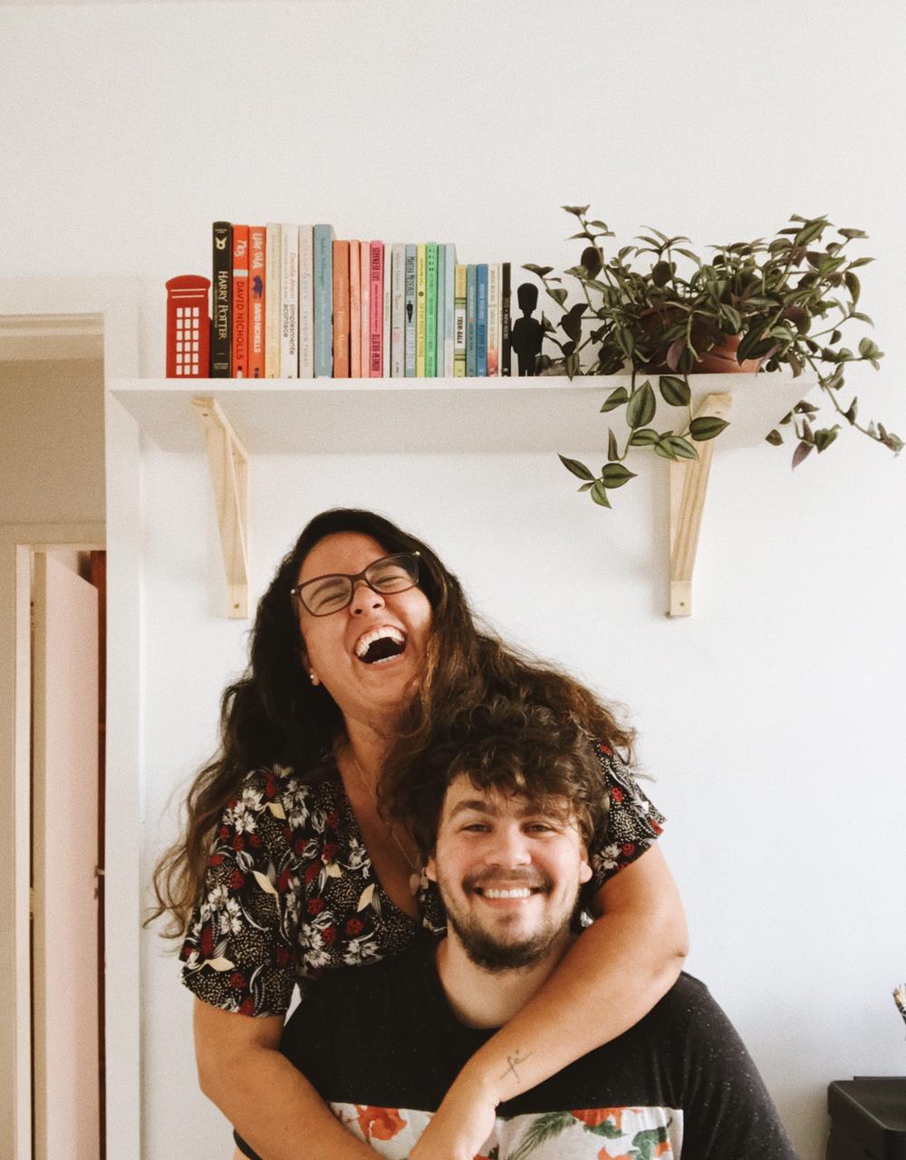 casal rindo em frente a uma prateleira de livros