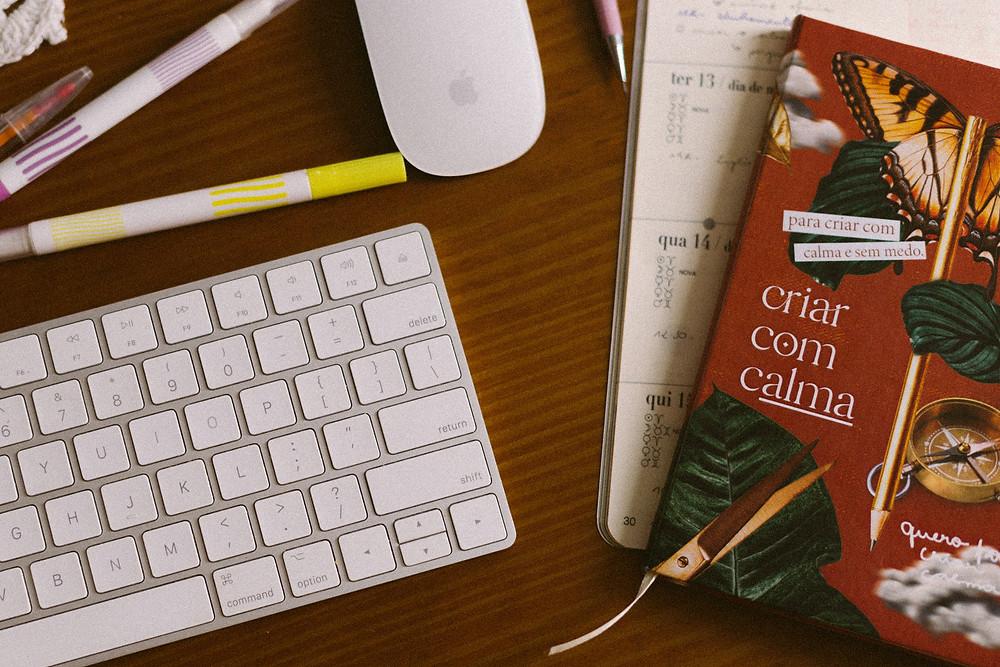 caderno da criativo produzido pela designer darlis studio, mesa de escritório bagunçada