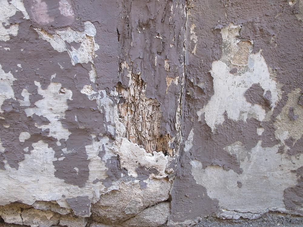 Abplatzungen an Putz und Anstrich einer Fachwerkfassade