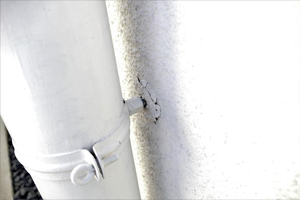 Putzschaden am Anschluss des Regenfallrohrs an die Außenwand.