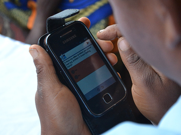 A community health worker uses a mobile application to support their home visit with clients.