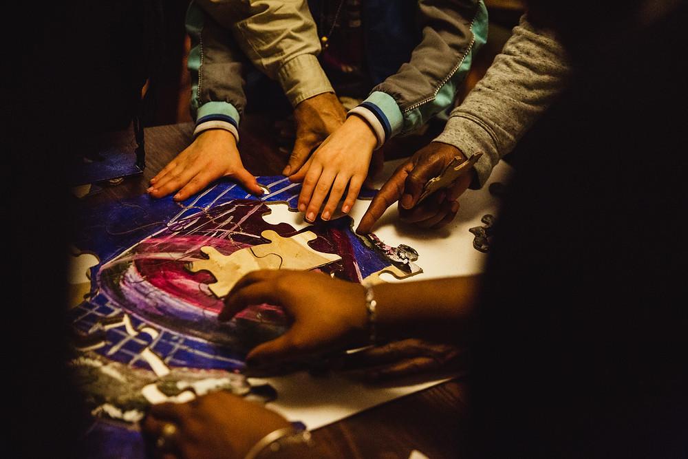 Hands building a puzzle