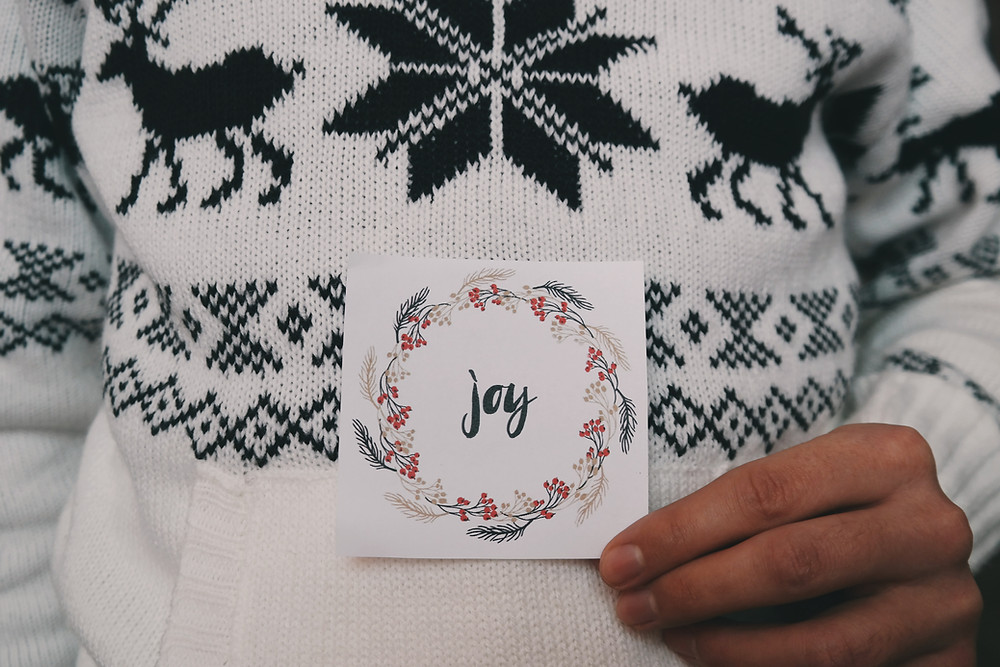 """Person holding a card with the word """"Joy"""" written on it"""