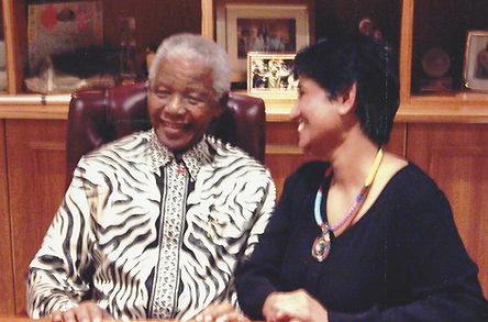 Black and white photo of Pregs Govender and Nelson Mandela at Pregs' 'favourite book reading'. Pregs is sitting with Madiba and smiling.