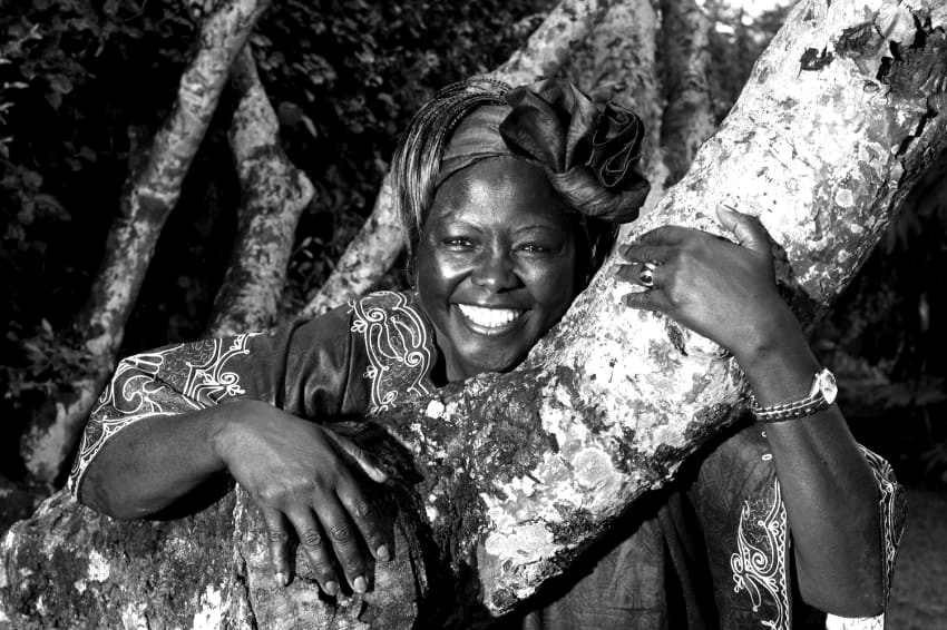 Black and white image of Wangari Maathai, earth warrior and writer, smiling at the camera, her arms wrapped around a tree.
